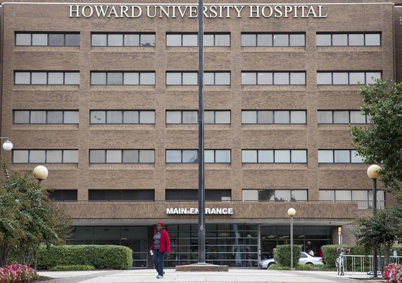 A woman walks in front of Howard University Hospital in Washington October 3, 2014. Howard University Hospital has admitted a patient with possible symptoms of the deadly Ebola virus