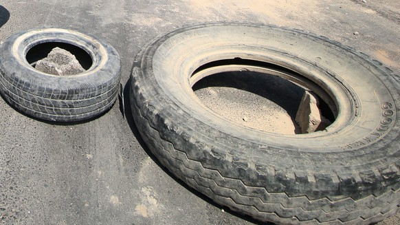 epa06893297 Iraqi protesters use Tires and concrete blocks to close a road during a protest at Hakimiyah, south of Basra city, southern Iraq, 16 July 2018. The protests hit several provinces in Iraq especialy in Basra over unemployment, the rising cost of living, and lack of basic services. Protests escalated after a protester was killed by security forces in Basra, as the demonstrators set tyres ablaze to block roads and tried to storm government installations. At least 10 protesters killed and more than 250 injured during the clashes between the security forces and the protesters in Basra, Mesan, and Najaf, Medical sources said.  EPA/HAIDER AL-ASSADEE