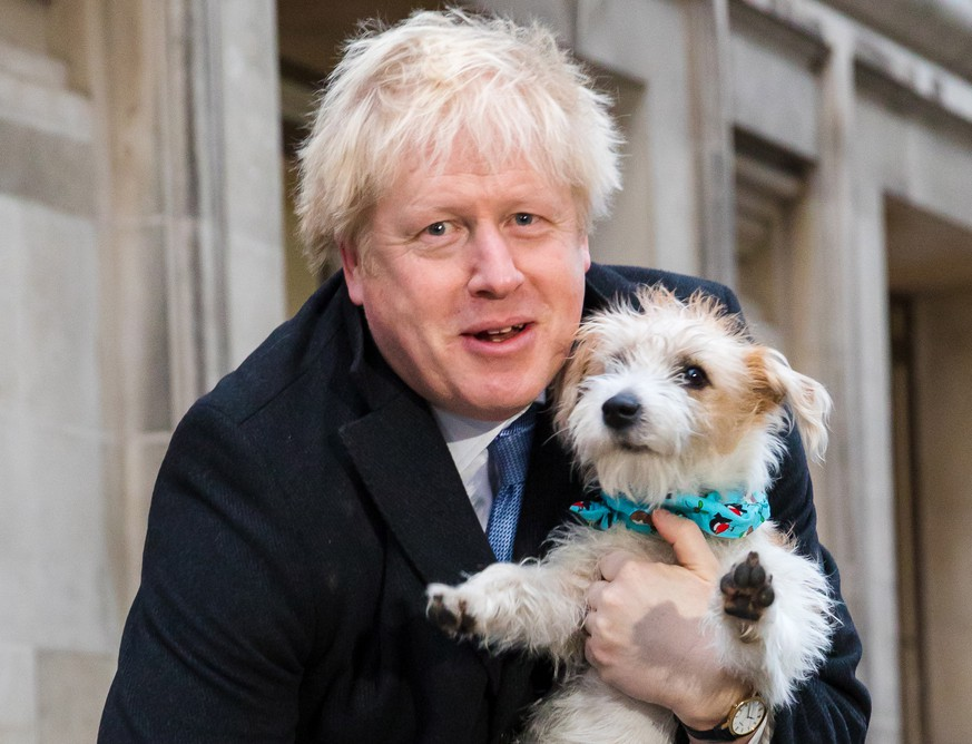 epaselect epa08064553 Britain's Prime Minster Boris Johnson leaves the polling station after casting his vote with his dog Dylan, during the general election in London, Britain, 12 December 2019. Britons go to the polls on 12 December 2019 in a general election to vote for a new parliament.  EPA/VICKIE FLORES