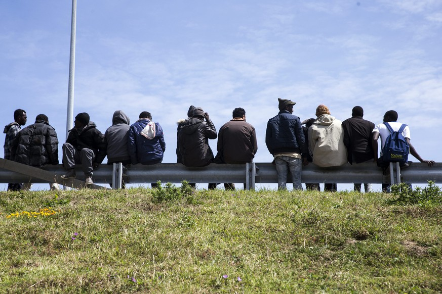 epa04818050 Migrants sit on a security rail of the access road to the Channel Tunnel in wait for trucks to jump on in order to reach Britain through the Channel Tunnel in Calais, France, 25 June 2015. The blockade of the port provoked a huge traffic jam of trucks, a golden opportunity for migrants to jump in and try to reach Britain. Several thousand refugees live in atrocious conditions in the so-called Calais Jungle makeshift camp. They have made it to Europe, often facing extreme hazards on the way, only to end up stranded in the northern French port.  EPA/ETIENNE LAURENT