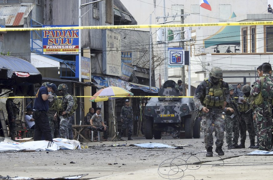 Police investigators and soldiers attend the scene after two bombs exploded outside a Roman Catholic cathedral in Jolo, the capital of Sulu province in southern Philippines, Sunday, Jan. 27, 2019. Two bombs minutes apart tore through a Roman Catholic cathedral on a southern Philippine island where Muslim militants are active, killing at least 20 people and wounding more than 80 others during a Sunday Mass, officials said. (AP Photo/Nickee Butlangan)