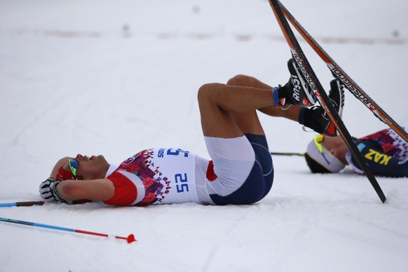 Chris Andre Jespersen of Norway lies in the snow after finishing the men's cross country skiing 15km classic competition at the XXII Winter Olympics 2014 Sochi in Krasnaya Polyana, Russia, on Friday, February 14, 2014. (KEYSTONE/Peter Klaunzer)