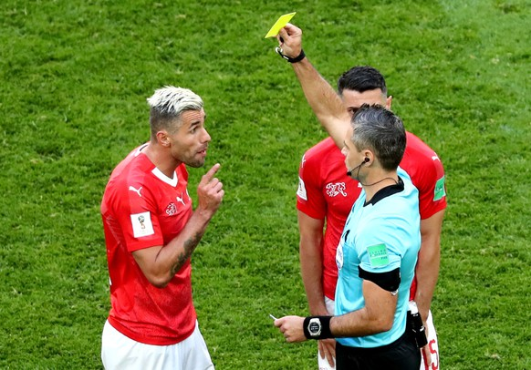 epa06861197 Valon Behrami of Switzerland (L) is booked by  Slovenian referee Damir Skomina (R) during the FIFA World Cup 2018 round of 16 soccer match between Sweden and Switzerland in St.Petersburg, Russia, 03 July 2018.