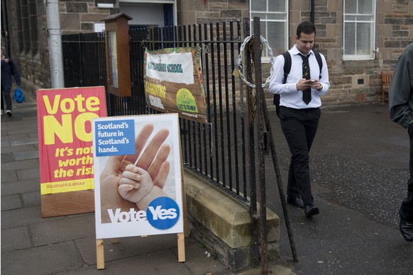 A school pupil walks away from a polling place after casting his vote, as anyone aged over 16 can vote in the Scottish independence referendum, in Edinburgh, Scotland, Thursday, Sept. 18, 2014.  Polls have opened across Scotland in a referendum that will decide whether the country leaves its 307-year-old union with England and becomes an independent state.  (AP Photo/Matt Dunham)