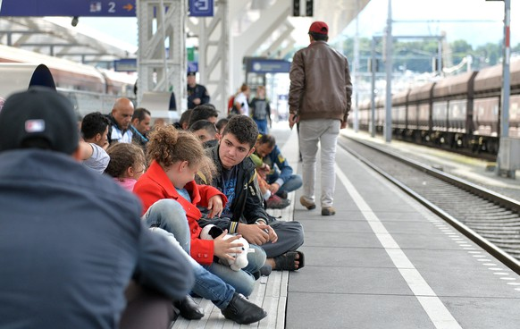 epa04931533 Refugees wait for more trains going to Germany at the main railway station in Salzburg, Austria, 15 September 2015. Train service between Germany and Austria resumed early 14 September after halting the connection the previous evening as part of emergency border measures imposed by Germany in a bid to stem the tide of refugees entering the country.  EPA/BARBARA GINDL