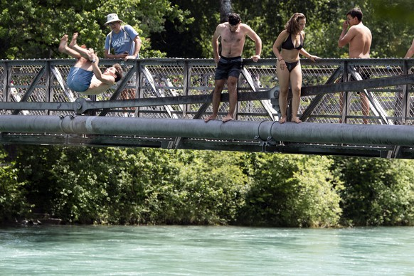 epa07672574 People jump into the 18 degree cold Aare River, in Bern, Switzerland, 25 June 2019. The forecasts predict hot weather in Switzerland with the maximum temperature at 38 degrees Celsius.  EPA/PETER SCHNEIDER