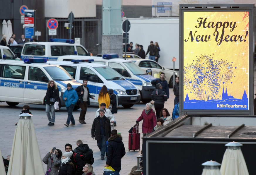 epa05691734 A 'Happy New Year' sign is on display near parked police vehicles in front of the Cologne central station in Cologne, Germany, 30 December 2016. As a result of the mass sexual assaults on New Year's Eve 2015, Cologne police are to deploy 10 times as many police officers, use video surveillance and create a firework-free zone near the Cathedral this year.  EPA/HENNING KAISER