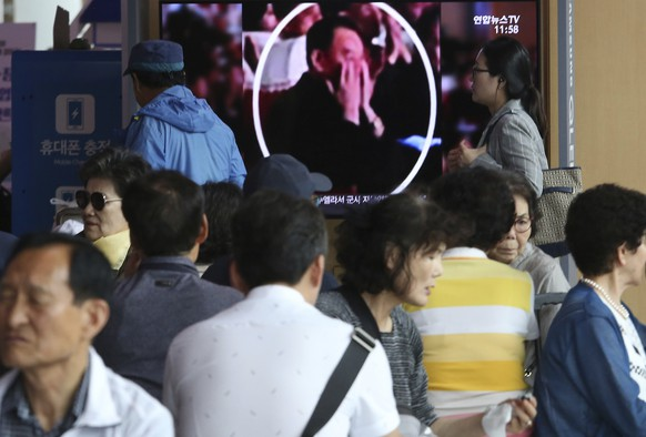 People watch a TV screen showing an image of senior North Korean official Kim Yong Chol in a musical performance by the wives of Korean People's Army officers in North Korea during a news program at the Seoul Railway Station in Seoul, South Korea, Monday, June 3, 2019. A senior North Korean official who had been reported as purged over the failed nuclear summit with Washington was shown in state media on Monday enjoying a concert alongside leader Kim Jong Un. (AP Photo/Ahn Young-joon)