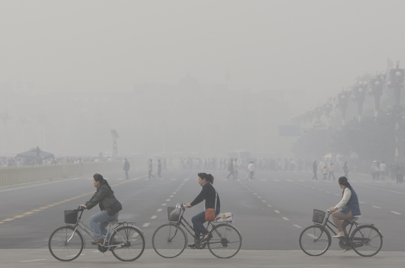 Chinese cycle through smog and pollution over Beijing's Tiananmen Square Thursday , May 1, 2008. (AP Photo/Oded Balilty)