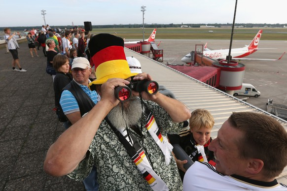 A German fan uses binoculars as he stands on the visitors terrace at Berlin airport Tegel on July 15, 2014, where the plane of German national football team is expected on their way back from Brazil after they won the FIFA World Cup 2014. The team comes to Berlin for a victory parade at landmark Brandenburg Gate to celebrate their fourth World Cup title, after their 1-0 win over Argentina on July 13, 2014 in Rio de Janeiro in the FIFA World Cup Brazil final game .
