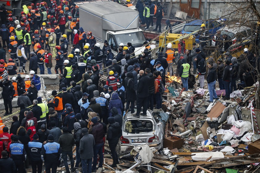 People watch rescue workers searching for survivors in the rubble of an eight-story building which collapsed two days earlier in Istanbul, Friday, Feb. 8, 2019. Turkish rescue workers on Friday pulled out a 16-year-old boy from the rubble of an eight-story apartment building in Istanbul two days after it collapsed, Turkey's interior minister Suleyman Soylu said. (AP Photo/Emrah Gurel)