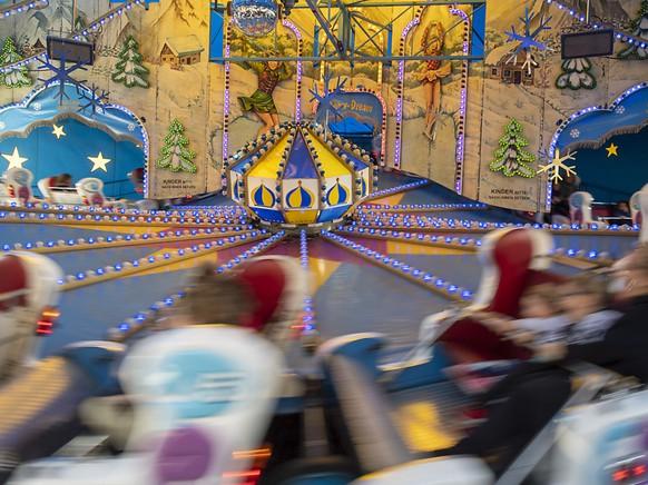 """Besucher auf dem """"Snow Dream"""" wirbeln herum an der 549. Herbstmesse in Basel."""