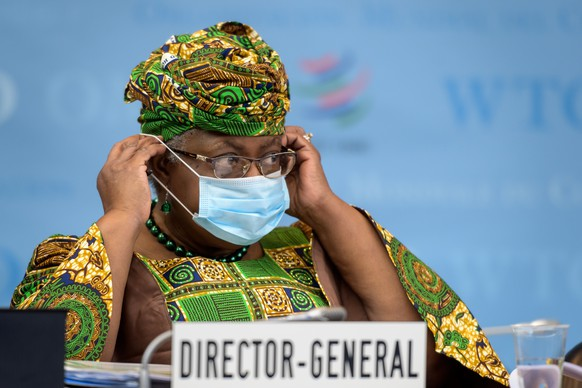 New Director-General of the World Trade Organisation Ngozi Okonjo-Iweala adjustes her facemask as a preventive measure against the Covid-19 coronavirus during a session of the WTO General Council upon her arrival at the WTO headquarters to take office in Geneva, Switzerland, Monday, March 1, 2021. Nigeria's Ngozi Okonjo-Iweala takes the reins of the WTO amid hope she will infuse the beleaguered body with fresh momentum to address towering challenges and a pandemic-fuelled global economic crisis. (Fabrice Coffrini/Pool/Keystone via AP)