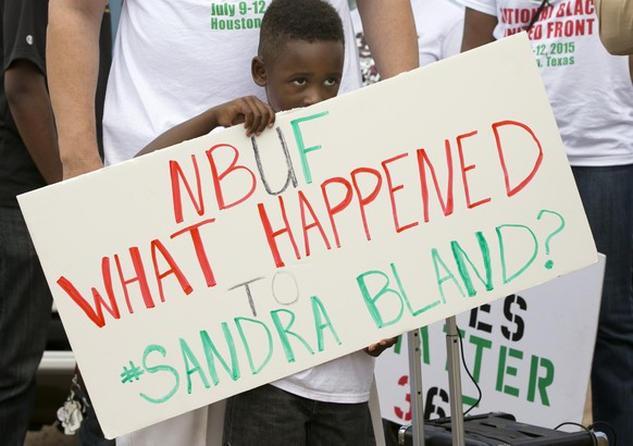 William Mitchell, 5, of Houston, holds a sign at a rally at the Waller County Jail in Hempstead, Texas, Friday, July 17, 2015, to protest the death of Sandra Bland, who was found dead in the jail. Waller County District Attorney Elton Mathis said there were no cameras in Bland's jail cell to show if the Illinois woman hanged herself in the lockup as a medical examiner has ruled. Her relatives and supporters dispute the finding.  (Jay Janner/Austin American-Statesman via AP)  AUSTIN CHRONICLE OUT, COMMUNITY IMPACT OUT, INTERNET AND TV MUST CREDIT PHOTOGRAPHER AND STATESMAN.COM, MAGS OUT; MANDATORY CREDIT