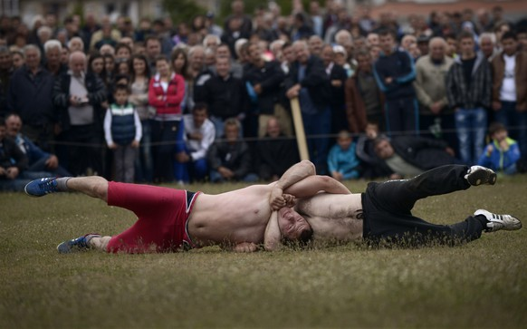 Competitors are locked into a strangulation during a traditional wrestling tournament, part of a holiday marking the circumcisions of young boys in the village of Draginovo, some 180km south-east of Sofia on May 04, 2014.  More than 100 boys were circumcised during a traditional ceremony in the small mountain village. AFP PHOTO / NIKOLAY DOYCHINOV