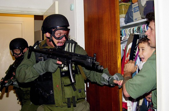 JAHRESRUECKBLICK 2000: AUSLAND: USA KUBA ELIAN - In this third of seven sequential photos, fisherman Donato Dalrymple holds 6-year-old Elian Gonzalez inside the bedroom of Lazaro Gonzalez during the pre-dawn hours Saturday, April 22, 2000, as Border Patrol agents stormed the Miami home to seize custody of the  boy.  (KEYSTONE/AP Photo/Alan Diaz)    [NY127]