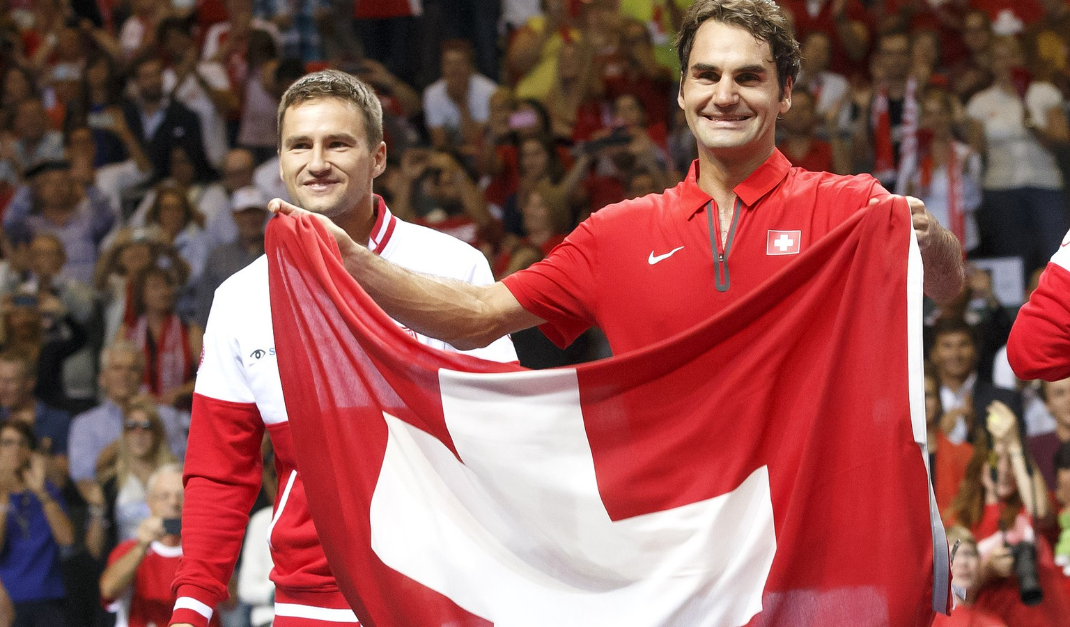 Roger Federer, right, of Switzerland, celebrates next to his teammate Marco Chiudinelli, left, with a Swiss flag after beating the Italy, at the Davis Cup World Group Semifinal match between Switzerland and Italy, at Palexpo, in Geneva, Switzerland, Sunday, September 14, 2014. (KEYSTONE/Salvatore Di Nolfi)