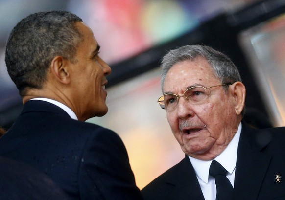 U.S. President Barack Obama (L) greets Cuba's President Raul Castro before giving his speech at the memorial service for late South African President Nelson Mandela in Johannesburg in this December 10, 2013 file photo. The United States and Cuba agreed on December 17, 2014 to restore diplomatic ties that Washington severed more than 50 years ago, and Obama called for an end to the long economic embargo against its old Cold War enemy. After 18 months of secret talks, Obama and Castro agreed in a phone call on December 16 on a breakthrough prisoner exchange, the opening of embassies in each other's countries, and an easing of some restrictions on commerce. REUTERS/Kai Pfaffenbach/files (SOUTH AFRICA - Tags: POLITICS BUSINESS)