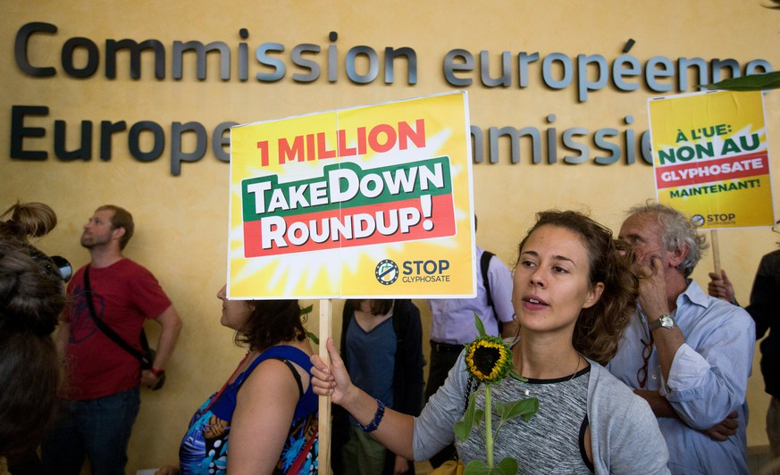 epa06096435 A woman holds a banner reading: '1 Million TakeDown Roundup!' to protest the use of the 'Glyphosate' herbicide in front of the seat of the European Commission at the Berlaymont building in Brussels, Belgium, 19 July 2017. The protest was held in the context of a debate within the European institutions, on whether or not to ban 'Glyphosate', a braodband hebicide which some scientists regard as being highly carcinogenic.  EPA/STEPHANIE LECOCQ