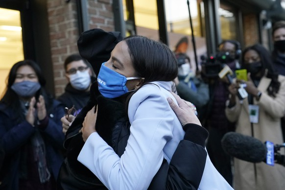 U.S. Rep. Alexandria Ocasio-Cortez, D-N.Y., right, embraces New York State Senator Alessandra Biaggi, a Democrat who represents the Working Families Party, while speaking to members of her staff and volunteers who helped with her campaign to get out the vote, Tuesday, Nov. 3, 2020, outside her offices in the Bronx borough of New York. (AP Photo/Kathy Willens) Alexandria Ocasio-Cortez,Alessandra Biaggi