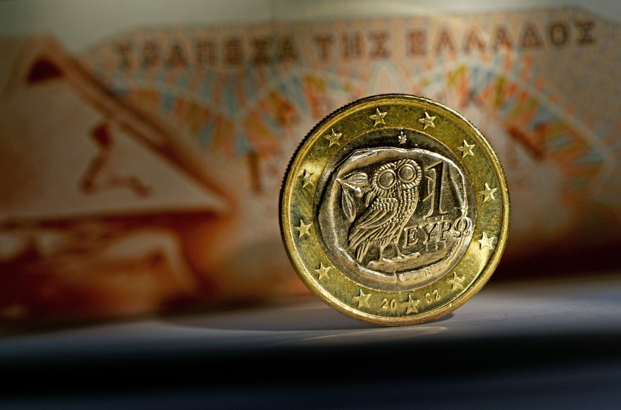 epa04624069 A close-up of a euro coin from Greece in front of a 100 drachma banknote in Potsdam, Germany, 17 February 2015. Greece rejected a European demand on 16 February to request an extension of its existing bailout by the end of the week, but Finance Minister Varoufakis was confident that a solution would be found, despite two rounds of failed negotiations.  EPA/RALF HIRSCHBERGER