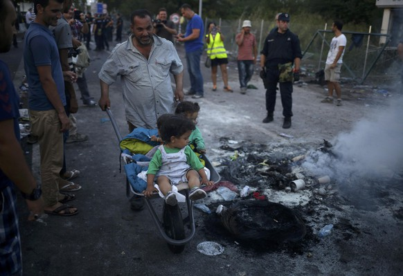A migrant pushes a cart with children inside as they pass burning remains of the clashes earlier today at the border with Hungary near the village of Horgos, Serbia, September 16, 2015.Twenty Hungarian policemen and two children were injured on the Hungarian border with Serbia in clashes that erupted after a group of migrants tried to break through the frontier, the prime minister's security adviser said. REUTERS/Stoyan Nenov