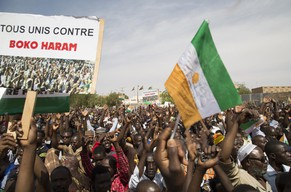 People march in support of the Niger army's war against Boko Haram in Niamey, February 17, 2015. Tens of thousands of people marched through Niger's capital Niamey on Tuesday to support the country's military following a series of attacks along the border with Nigeria carried out by Boko Haram militants. The sign reads