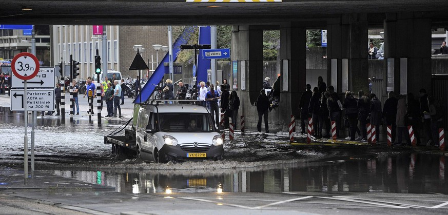 epa04919926 A car drives through hig waters after a burst water pipe created a lot of inconvenience in the surroundings of the Medical Centre and the VU (Free University) in Amsterdam, The Netherlands, 08 September 2015. The VUmc will evacuate around 500 of their patients. The bottom floor of the hospital was flooded with water, causing the electricity to partly fail.  EPA/EVERT ELZINGA