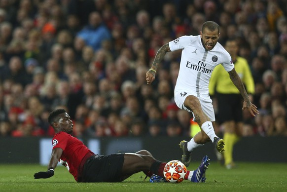 Manchester United's Paul Pogba, left, slides into tackle Paris Saint Germain's Dani Alves during the Champions League round of 16 soccer match between Manchester United and Paris Saint Germain at Old Trafford stadium in Manchester, England, Tuesday, Feb. 12,2019.(AP Photo/Dave Thompson)