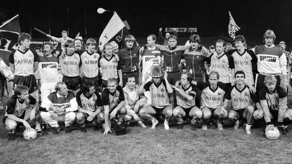 The team of the Young Boys celebrated the victory of the championship in Berne on 27 May 1986. Lars Lunde, in the middle, is enthusiastically pushing the championship cup over his head. (KEYSTONE/Str)  Die Mannschaft der Berner Young Boys feiert am 27. Mai 1986 in Bern den Sieg der Meisterschaft nach dem Spiel gegen den FC Zuerich. YB Stuermer Lars Lunde, Mitte, stuelpt sich vor Begeisterung den Meisterpokal ueber den Kopf. Die Mannschaft, stehend v.l.n.r. Rene Suter, unbekannt, Dario Zuffi, unbekannt, Robert Prytz,vier Spieler unbekannt, Juerg Wittwer, Alain Baumann, Walter Eichenberger; kniend v.l.n.r. Roland Schoenenberger, unbekannt, Georges Bregy, unbekannt, Trainer Alexander Manziara, Lars Lunde, Captain Jean-Marie Conz, Martin Weber, Urs Bamert und Torhueter Urs Zurbuchen. (KEYSTONE/Str)