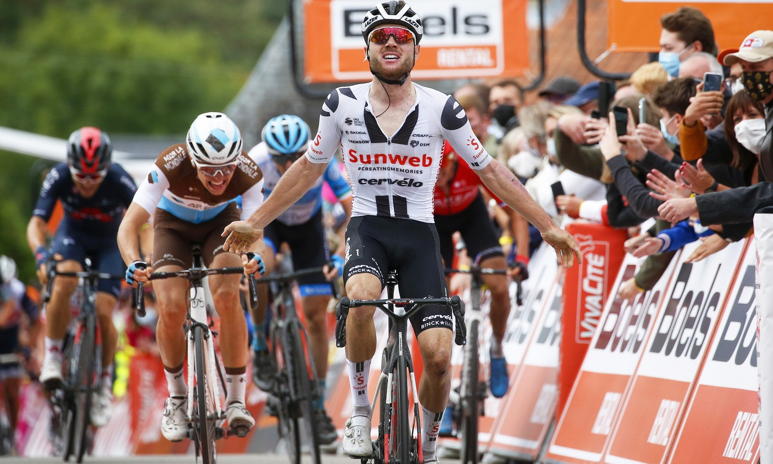 epa08708899 Swiss rider Marc Hirschi (C) of Team Sunweb celebrates  while crossing the finish line to win the 84th edition of the Fleche Wallonne one day cycling race over 202km from Herve to Huy, Belgium, 30 September 2020.  EPA/JULIEN WARNAND