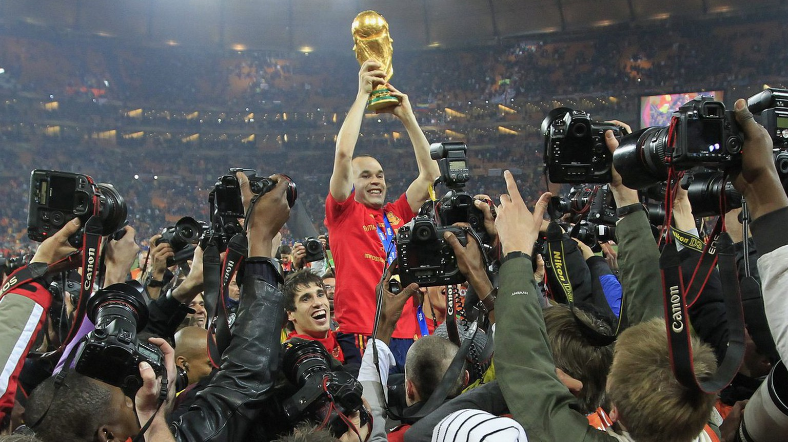 Spain's Andres Iniesta celebrates with the trophy after winning the 2010 FIFA soccer World Cup final between the Netherlands and Spain in the Soccer City Stadium in Johannesburg, South Africa, pictured on Sunday, July 11, 2010. (KEYSTONE/Peter Klaunzer)  EDITOR'S NOTE: Under terms of the World Cup journalist accreditation agreement, images from World Cup soccer matches may only be displayed on mobile devices at the end user's initiative and request, unpromted by any alert, update or other information pushed to the user's device. No trademark rights or rights of personality are conveyed with these images. All usage must comply with FIFA credential restrictions posted at http://www.ap.org/mediacredential/index.html