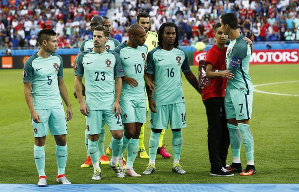 epa05411625 A young man (2nd R) joins Cristiano Ronaldo (R) and his Portuguese teammates on the pitch prior to the UEFA EURO 2016 semi final match between Portugal and Wales at Stade de Lyon in Lyon, France, 06 July 2016.  (RESTRICTIONS APPLY: For editorial news reporting purposes only. Not used for commercial or marketing purposes without prior written approval of UEFA. Images must appear as still images and must not emulate match action video footage. Photographs published in online publications (whether via the Internet or otherwise) shall have an interval of at least 20 seconds between the posting.)  EPA/IAN LANGSDON   EDITORIAL USE ONLY