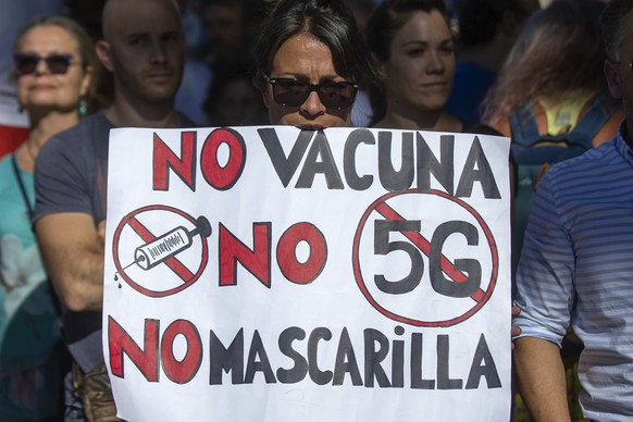 "Demonstrators attend a protest against nationwide restrictions against COVID-19 in Madrid, Spain, Sunday, Aug. 16, 2020. A banner reads in Spanish ""No vaccine No 5G No mask"". (AP Photo/Andrea Comas)"