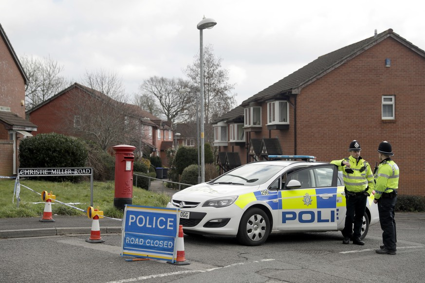 Police officers stand guard at the bottom of the road where former Russian double agent Sergei Skripal lives in Salisbury, England, Tuesday, March 13, 2018. The use of Russian-developed nerve agent Novichok to poison ex-spy Sergei Skripal and his daughter makes it