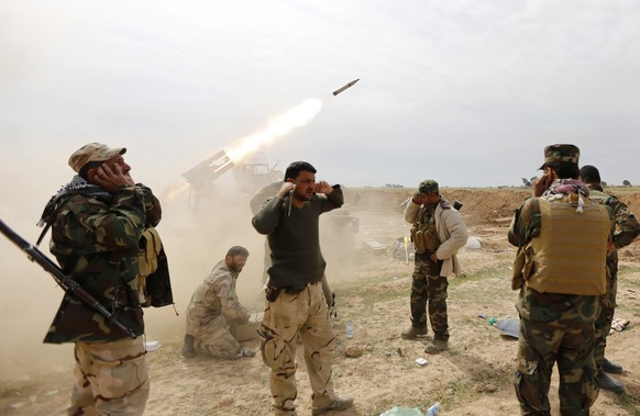 Shi'ite fighters cover their ears as a rocket is launched during a clash with Islamic State militants in the town of al-Alam March 9, 2015. Just north of Tikrit, home city of executed Sunni former president Saddam Hussein, Iraqi security forces and Shi'ite militia fighters began an offensive against Islamic State to regain control over the town of al-Alam.   REUTERS/Thaier Al-Sudani (IRAQ - Tags: POLITICS CIVIL UNREST CONFLICT)