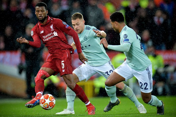 epa07381664 Liverpool's Georginio Wijnaldum (L) in action against Bayern players Joshua Kimmich (C) and Serge Gnabry (R) during the UEFA Champions League round of 16 first leg soccer match between Liverpool FC and FC Bayern Muenchen at the Anfield in Liverpool, Britain, 19 February 2019.  EPA/PETER POWELL
