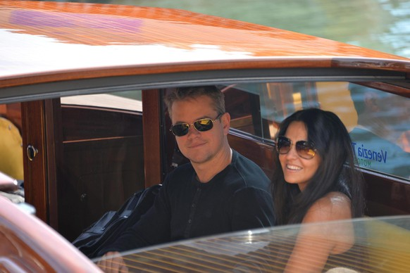 epa04418316 US actor Matt Damon (C) and his wife Luciana Barroso (R) get on board of a boat after landing at Nicelli airport, at Venice Lido, Italy, 26 September 2014. According to media reports, the wedding of US actor George Clooney and Lebanese-British lawyer Amal Alamuddin is to take place in Venice this weekend.  EPA/ANDREA MEROLA