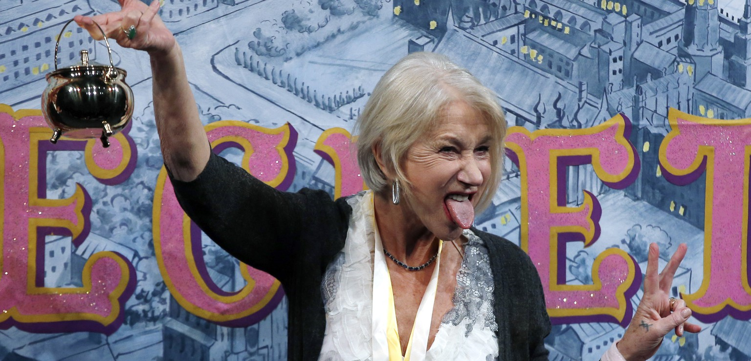 Actress Helen Mirren holds the Hasty Pudding Pot aloft and sticks her tongue out during her roast as woman of the year by Harvard University's Hasty Pudding Theatricals in Cambridge, Mass., Thursday, Jan. 30, 2014. (AP Photo)