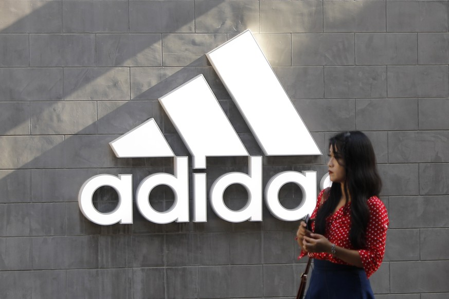 epa07591449 A Chinese woman walks past a logo of Adidas outside Adidas store in Beijing, China, 22 May 2019. A letter signed by 173 companies which including Nike, Adidas, says the US President's decision to raise import tariffs to 25 percent will disproportionately affect the working class after Donald J. Trump increased levies on 200 billion US dollars worth of Chinese imports into the US from 10 percent to 25 percent.  EPA/WU HONG