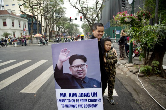 A boy with the hair-cut of North Korean leader Kim Jong Un look alike stands with a portrait of him outside Melia Hotel where Kim is staying in Hanoi, Vietnam, Wednesday, Feb. 27, 2019. Kim remained in his locked-down hotel for a large part of the day but was expected to take in some sights before Kim and U.S. President Donald Trump open their nuclear summit with private talks and a social dinner. (AP Photo/Gemunu Amarasinghe)