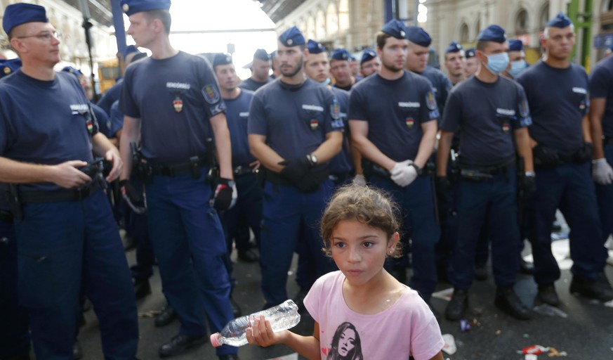 A girl walks past a line of Hungarian police at the main Eastern Railway station in Budapest, Hungary, September 1, 2015. Hungary closed Budapest's main Eastern Railway station on Tuesday morning with no trains departing or arriving until further notice, a spokesman for state railway company MAV said. There are hundreds of migrants waiting at the station. People have been told to leave the station and police have lined up at the main entrance, national news agency MTI reported. REUTERS/Laszlo Balogh