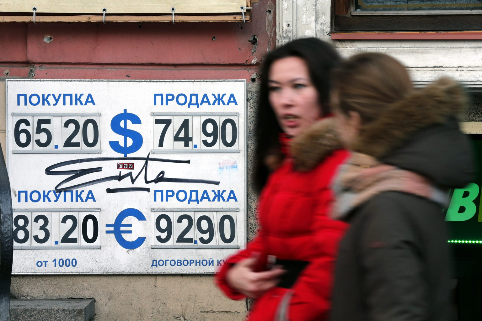 epa04531198 People walk near a foreign currency exchange office in St. Petersburg, Russia, 16 December 2014. Russian currency dropped to 100 rubles to one euro, more then 25 per cent per a day. Russia's Central bank raised refinancing rate up to 17 per cent per a year (plus 650 basic points).  EPA/ANATOLY MALTSEV