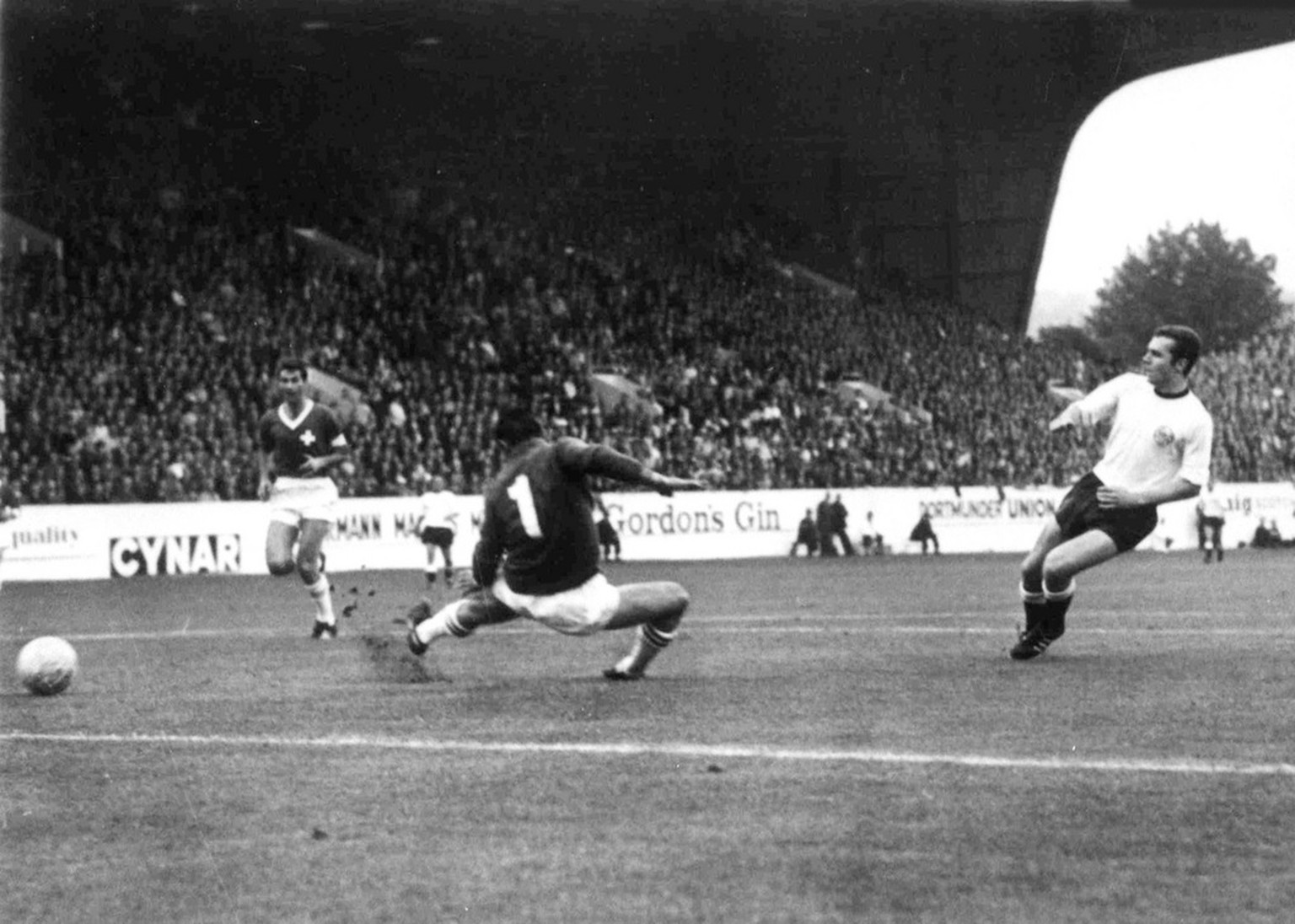 West Germany's Franz Beckenbauer, right, scores his teams fourth goal against Switzerland in the Football World Cup match at Hillsborough Stadium, Sheffield, on July 12, 1966. Swiss goalkeeper Charles Elsener attempts to stop the ball. West Germany defeated Switzerland 5-0. (AP Photo/Bippa)
