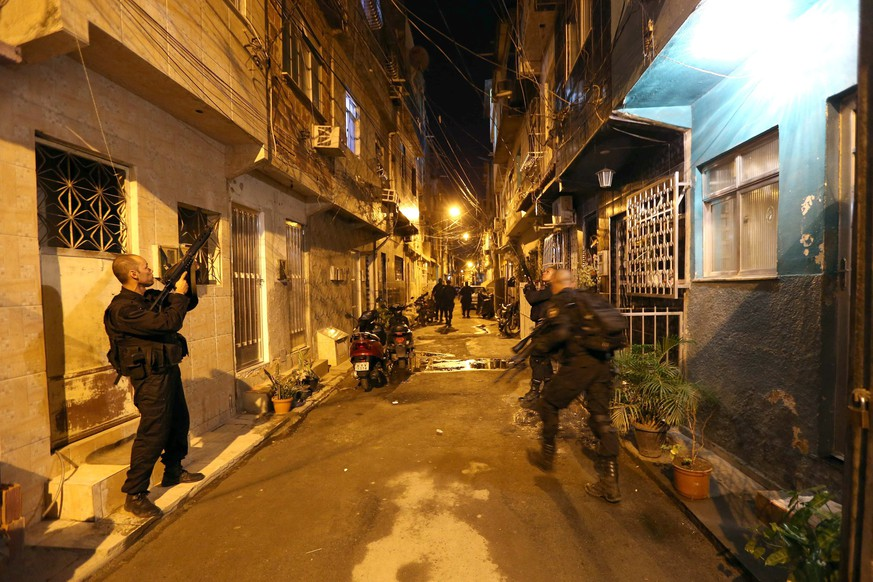 epaselect epa04146982 Brazilian policemen advance during a police raid at Mare favela cluster, in Rio de Janeiro, Brazil, 30 March 2014. Almost 1,200 policemen backed by Brazilian Army's 21 armoured vehicles occupied peacefully the Mare favela complex, considered the most dangerous in Rio de Janeiro as it's the main drug distribution center of the city because of its strategic location between the bay of Guanabara and the two main roads leading to the airport. The operation was carried out days after Brazilian President Dilma Roussef signed a decree that states the Army's presence at the Mare favelas until the end of FIFA's Brazil 2014 World Cup.  EPA/MARCELO SAYAO