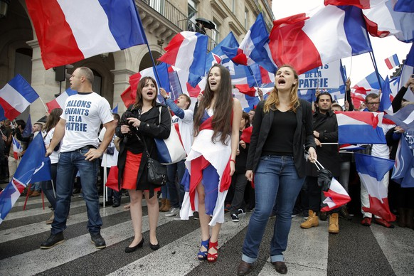 France's far-right National Front demonstrators chant slogans during their annual May Day march, in Paris, France, Friday, May 1, 2015. France's far-right National Front is holding its annual May Day march, but for the first time the party's founder Jean-Marie Le Pen _ on the outs with his daughter who presides over the party _is not taking a seat at the tribune. (AP Photo/Francois Mori)