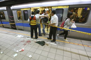 Officials block parts of the scene of a knife attack on a subway platform, in Taipei, Taiwan, Wednesday, May 21, 2014. A drunken university student wielding a knife attacked riders aboard a subway train in Taiwan's capital on Wednesday, killing three people and injuring nearly two dozen others, police and local media said.(AP Photo)