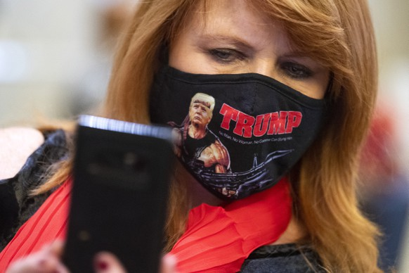 epa08797426 A woman takes a selfie of her self wearing a Rambo style Trump mask while attending an election night rally for Republican Senator from Georgia Kelly Loeffler, held in Atlanta, Georgia, USA, 03 November 2020. Loeffler's main opponents in the Senate race are Republican Representative from Georgia Doug Collins and Democrat Reverend Raphael Warnock. Americans vote on Election Day to choose between re-electing Donald J. Trump or electing Joe Biden as the 46th President of the United States to serve from 2021 through 2024.  EPA/JOHN AMIS