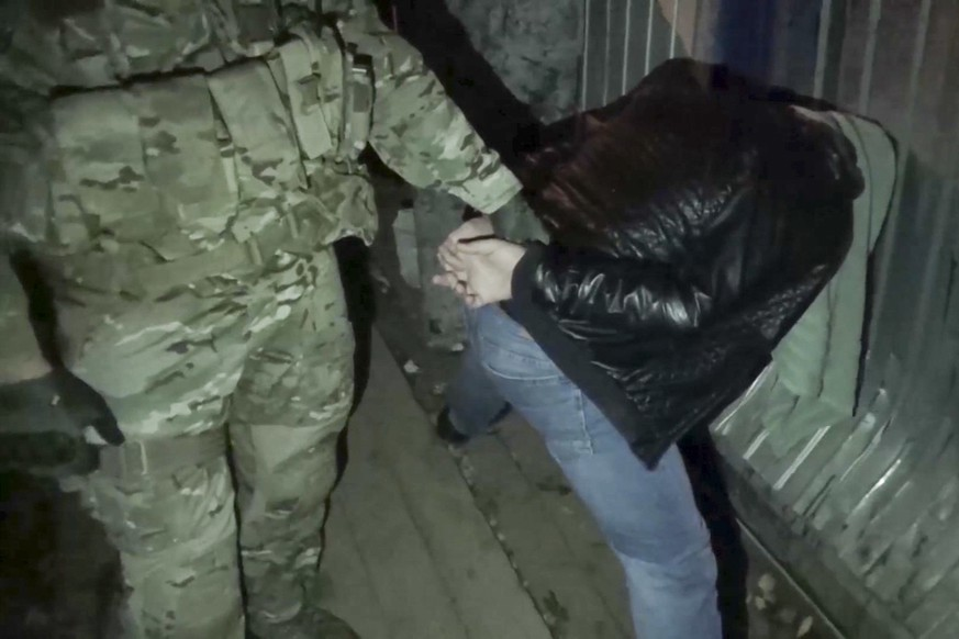 In this video grab provided by the RU-RTR Russian television via APTN on Monday, Oct. 2, 2017, FSB operatives detain a man, outside Moscow on Saturday, Sept. 30 2017. Russia's top domestic intelligence agency says it has detained members of a sleeper cell of the Islamic State group and foiled a series of terrorist attacks. (RU-RTR Russian Television/via AP)
