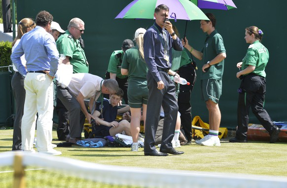 epa04826524 Play is interrupted on an outside court as medics attend to a ball boy who collapsed during a hot day at the Wimbledon Championships at the All England Lawn Tennis Club, in London, Britain, 01 July 2015.  EPA/GERRY PENNY
